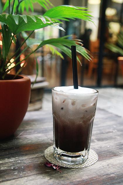 6 Oromia coffee  Orimia mang phong cách của một quán cà phê phương Tây với lối kiến trúc tinh tế đặc trưng, màu sắc trang nhã nhưng không quá cầu kỳ. Quán còn ghi điểm bởi những bản nhạc lãng mạn được mở liên tục, dù ngồi trong hay ngoài thì bạn đều nghe được những giai điệu ấy. Vào buổi đêm, khi những bóng đèn vàng được thắp lên, bạn sẽ lại bước vào một thế giới khác hoàn khác. Bên cạnh đó, quán còn mang đến cảm giác gần gũi với thiên nhiên cho thực khách khi khắp nơi trong quán đều được phủ bởi màu xanh của cây cối. Ngay bước chân đầu tiên vào quán, bạn đã bắt gặp một ao cá cùng các phím đá làm lối đi, tạo cảm giác như lạc vào chốn thiên nhiên hoang sơ.  Từ những món cà phê truyền thống cho đến những món đá xay, so-da mang đậm phong cách trẻ trung, bắt kịp xu hướng. Giá trung bình ở quán dao động từ 40.000 đồng đến 150.000 đồng. Ảnh: Phong Vinh
