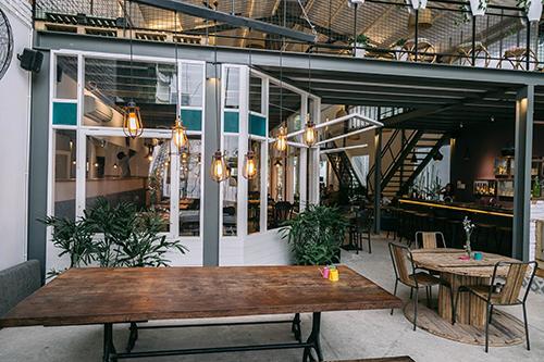 9  Kokois coffee  Không đơn giản nhưng với tiêu chí đẹp mắt, sang trọng thì Kokois là địa chỉ cà phê hiếm hoi được đánh giá mang tính nghệ thuật sắp đặt cao ở Sài Gòn. Không gian quán nằm trong một tầng lửng, thiết kế như một nhà kho thực thụ. Lồng vào đó là khu vực bar trong và ngoài trời. Những vật trang trí được giữ nguyên theo ý tưởng những chiếc bàn thép công nghiệp và container vận tải. Đặt chân vào bên trong, thực khách sẽ cảm giác như lạc vào một nơi hoàn toàn tách biệt với thiên nhiên, cây cối bao quanh tạo sự gần gũi, thoáng đãng. Ảnh: Cao Trí