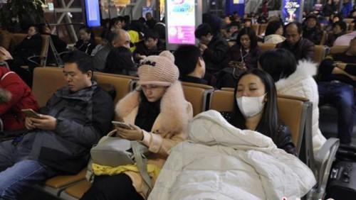 Mắc kẹt trong nhiều giờ khiến các hành khách mệt mỏi ngủ ở ghế sân bay, nhiều người đứng ăn mì ăn liền, trong khi các thùng hành lý chất đống trên đường băng, bên cạnh những chiếc máy bay đang chờ được cất cánh. Ảnh: Chinanews.