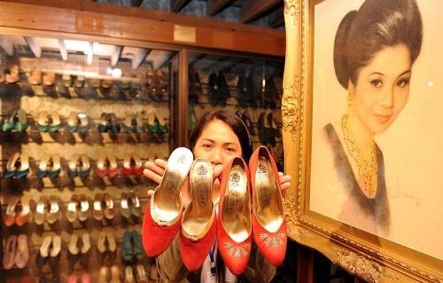 Một nhân viên bảo tàng cho khách xem một số đôi giày của chính vợ phó tổng thống Imelda Marcos, cạnh bức chân dung vẽ bà trong bảo tàng giày ở Manila. Ảnh: Ted Ajibe.