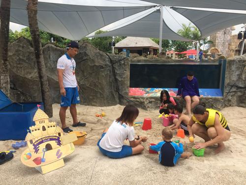 Bé học xây lâu đài cát với các giáo viên hướng dẫn
