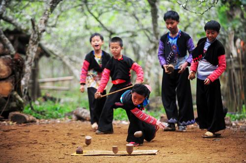 Những đứa trẻ người Mông say sưa với trò chơi quay, dưới tán những cây mận nở hoa chi chít.. Ảnh: Mèo Già.