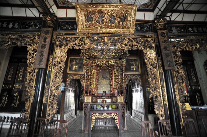 """<p class=""""Normal""""> Nội thất căn nhà cổ mang đậm màu sắc Trung Hoa với cánh cửa, cột nhà, bàn thờ... sơn son thếp vàng, chạm trổ loan phượng rất sắc sảo và tinh tế. Chính giữa là ban thờ Quan Công, một vị tướng thời Tam Quốc.</p>"""