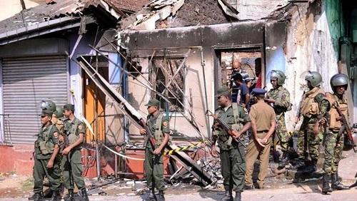 Lực lượng đặc nhiêm Sri Lanka đứng gác bên một căn nhà bị cháy ngày 6/3, sau cuộc đụng độ giữa hai cộng đồng tôn giáo tại Digana, quận trung tâm Kandy. Ảnh:Reuters.