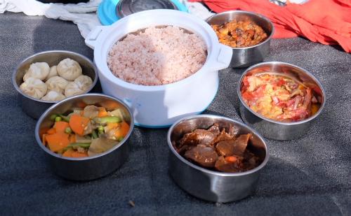 Bữa cơm do lái xe và hướng dẫn viên chuẩn bị cho hai người khách ăn cùng trong một buổi trekking. Cơm nấu từ gạo huyết rồng (red rice), bánh bao, rau củ xào, ớt nấu với phomat và một món thịt.