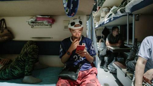 Kensuke đang mải mê ngồi xem điện thoại, anh trông trẻ hơn tuổi 40 của mình. KhiDmitry Medvedev