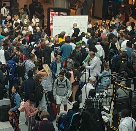 Nhân viên sân bay viết thông tin từng chuyến lên bảng trắng, một số hành khách khen ngợi sáng kiến này. Ảnh: Tamara Salem.