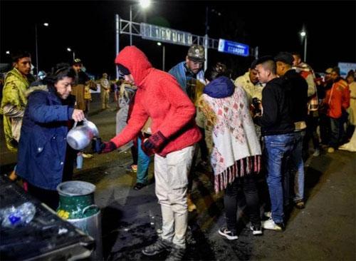 Người dân Venezuela đang nhận đồ ăn từ thiện từ nhóm người tình nguyện Colombia khi bị mắc kẹt ở biên giới và không thể nhập cảnh Ecuador. Ảnh: News.