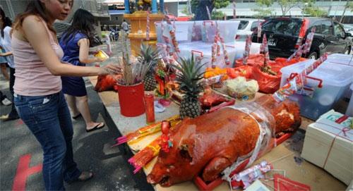 Người dân Singapore thường cúng lợn quay trong dịp rằm tháng 7. Ảnh: SCMP.