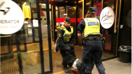 Cảnh sát Thuỵ Điển khiêng du khách ra khỏi khách sạn vì nghi họ là dân tị nạn. Nguồn: CGTN..