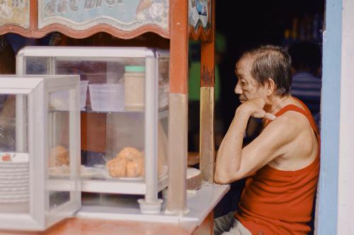 Ông Hà ngồi bên chiếc xe hủ tiếu đã gắn bó suốt 38 năm. Ảnh: Linh Sea.