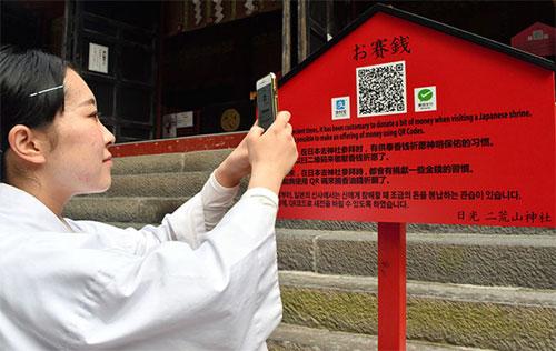 Du khách đến đền có thể quét mã QR để chuyển khoản tiền công đức. Ảnh: Asahi.
