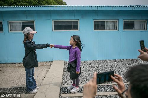 Khách nhí bắt chước cú bắt tay lịch sử tại khu phi quân sự DMZ giữa hai nhà lãnh đạo trên bán đảo Triều Tiên. Ảnh:CGTN.