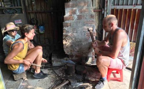Các du khách tham gia vào một buổi học làm dao tại làng Đa Sỹ, với giá tour là 34 USD một người.