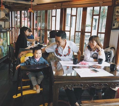 Hai vợ chồng anh Đăng, chị Uyên và bé Pai (tên gọi thân mật của cô con gái nhỏ). Pai đã được bố mẹ cho đi du lịch hàng chục chuyến trong nước và quốc tế khi còn rất nhỏ. Trên ảnh, cả nhà đang chụp ảnh trong quán trà Amei. Ảnh: NVCC.