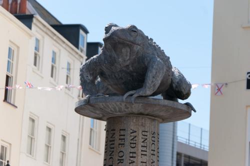 Bức tượng Cóc Jersey đặt trên nền một nhà tù cũ, với những tội danh và hình phạt theo luật của chính quyền. Ảnh:
