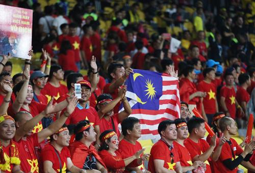 Các CĐV Việt Nam vẫy cờ và vỗ tay động viên khi các tuyển thủ Malaysia đi ngang qua ở phía dưới sân. Cử chỉ của họ nhận được hoan nghênh, từ khu vực khán đài bên cạnh của các CĐV chủ nhà. Ảnh: Đức Đồng.