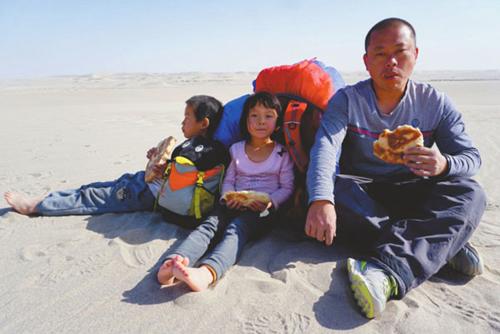 Wenwen (giữa) cùng bố và anh trai ngồi nghỉ trên sa mạc Lop Nur. Ảnh:West China City News.
