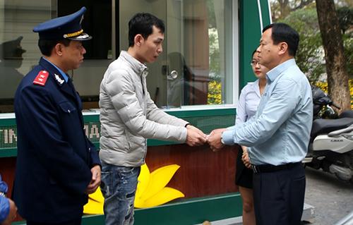 Tài xế Điệp (thứ hai từ trái qua) trả lại tiền thừa cho du khách thông qua đại diện Thanh tra Sở Du lịch Hà Nội. Ảnh: KTĐT.