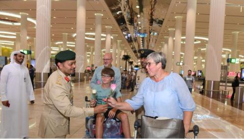 Khách Tây nhận hoa hồng từ cảnh sát tại sân bay Dubai. Ảnh:Cảnh sát Dubai.