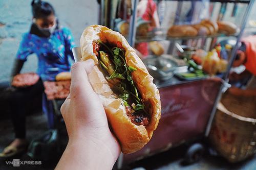 Bánh mì thịt nướng Nguyễn TrãiXe bánh mì nằm trong con hẻm nhỏ trên đường Nguyễn Trãi (quận 1) này từng được tạp chí du lịch Mỹ Condé Nast Traveler nhắc tới trong danh sách 12 món ăn đường phố ngon nhất thế giới. Hàng chỉ bán duy nhất một loại nhân là thịt nướng, và nước chan là một loại sốt đặc biệt thay vì tương như ở nơi khác. Thịt nướng bán ở đây là viên thịt heo băm nhuyễn trộn gia vị kèm nước sốt theo công thức riêng của chủ rồi đem nướng trên vỉ bếp than ngay tại chỗ. Bếp nướng thịt tỏa mùi thơm quyến rũ cũng chính là đặc điểm để thực khách tìm ra vị trí xe bánh mì trong hẻm nhỏ.Hàng bánh mì thịt nướng mở cửa từ 16h đến 21h và luôn đông nghẹt khách. Giá mỗi ổ là 20.000 đồng gồm 5 viên thịt, nước sốt và đồ chua.