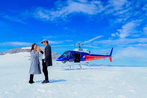 Vợ chồng Phan Anh uống champagne trên dòng sông băng sau khi đáp trực thăng. Ảnh: NVCC.