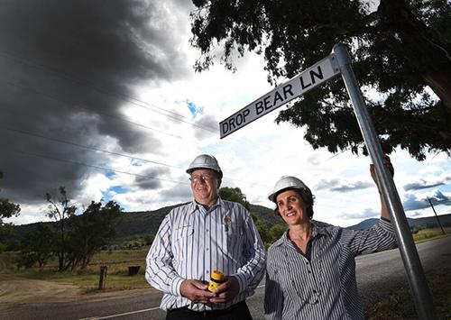 Thị trưởng Murray cầm trên tay thuốc chống gấu Vegemite bên cạnh cư dân địa phương Kylie Evans trong ngày gắn biển Drop Bear Lane. Tấm biển này bị đánh cắp năm 2017 và đã được thay thế ngay sau đó. Ảnh: Gareth Gardner.