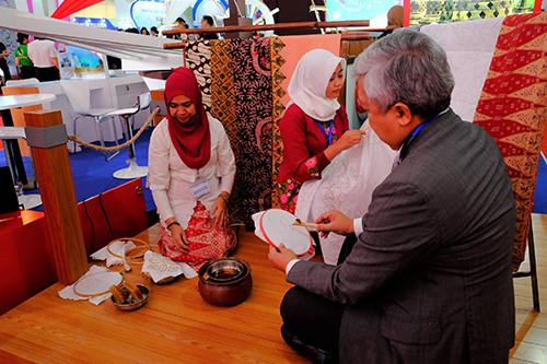 Du khách trải nghiệm làm vải batik truyền thống tại hội chợ năm ngoái. Ảnh: Hương Chi.