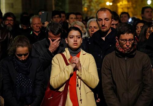 Người dân cầu nguyện khi chứng kiến lửa lan rộng trên mái nhà thờ. Ảnh:AP.