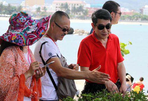 Người đàn ông Trung Quốc (áo trắng) thuyết trình tại danh thắng Hòn Chồng, Nha Trang. Ảnh: Xuân Ngọc