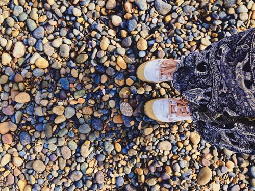 Bãi đá trơn nhẵn có nhiều màu sắc, khi ánh nắng chiếu vào sẽ khiến bờ biển rực rỡ. (Ảnh: Tâm Linh)