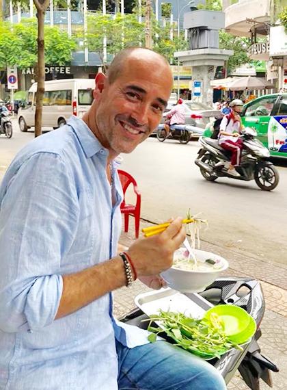 David thưởng thức phở tại một quán trên lề phố Sài Gòn.