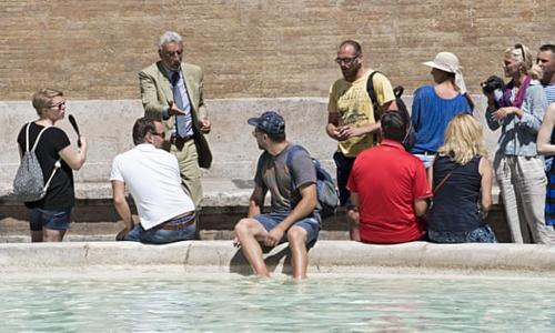 Ăn quá nhiều đồ ăn vặt cũng nằm trong tầm ngắm của chính quyền, những người không tử tế với khách du lịch làm rơi nước sốt cà chua và vụn mozzarella trên các tượng đài bằng đá cẩm thạch và travertine. Một du khách tắm chân trong Đài phun nước Trevi ở Rome. Ảnh: Maurizio Brambatti / EPA.