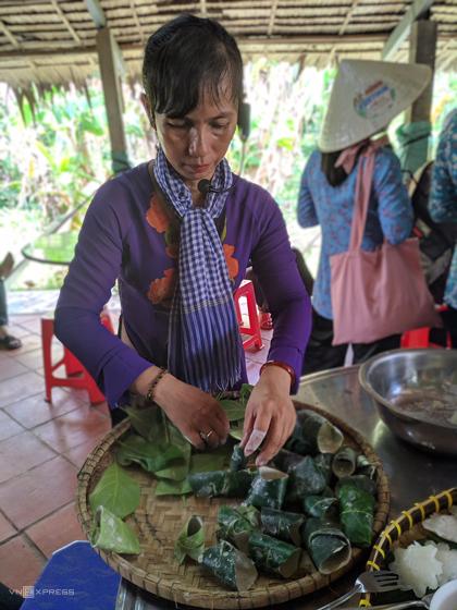 Người dân hướng dẫn kháchlàm bánh ở Cồn Sơn, Cần Thơ.