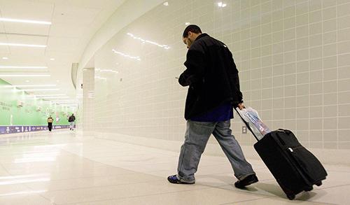 Du khách chỉ cần tự kéo hành lý là có thể tiết kiệm một vài đôla khi đi du lịch. Ảnh: Rusty Finch.