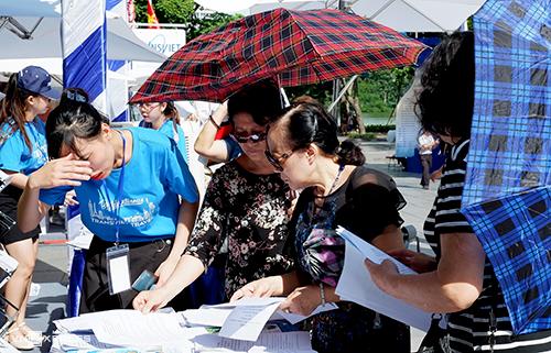 Vì tiết trời nắng nóng, nhiều khách mang theo ô, mũ, áo chống nắng khi xếp hàng tìm hiểu về các tour du lịch.Ảnh:Lan Hương.