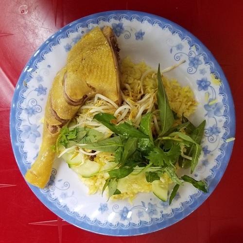 Phần đùi gà vàng óng được xếp cùng cơm, trang trí rau dăm, giá, hành củ muối. Ảnh: Tung Nguyen.