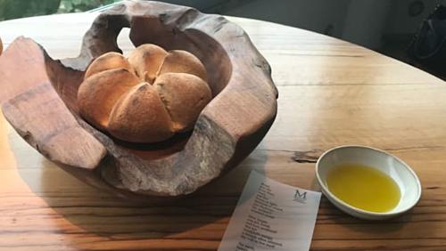 Món bánh mỳ ăn kèm dầu ô liu, chanh, gừng và một bài thơ của nhà thơ nổi tiếng người Chile. Ảnh: CNN.