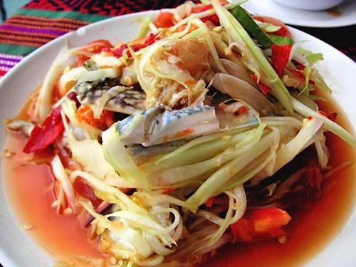 Som Tam (gỏi đu đủ ghẹ sống)Đâylà món ăn nổi tiếng của Tháivào top 50 món ngon nhất thế giới. Nguyên liệu chính của Som Tam là đu đủ xanh và ghẹ sống. Đu đủ được bào sợi, trộn cùngđậu đũa, chuối xanh, cóc, xoài xanh, bắp cải, dưa chuột, lạc rang và các loại gia vị khác. Ghẹ nguyên con tươi sống ngâm trong hỗn hợp muối, chanh, khổ qua, ớt cay, sau đó sẽ được cắt làm đôi hoặc bẻ thành nhiều miếng nhỏ, trộn cùng các nguyên liệu còn lại.Ảnh: Panix.