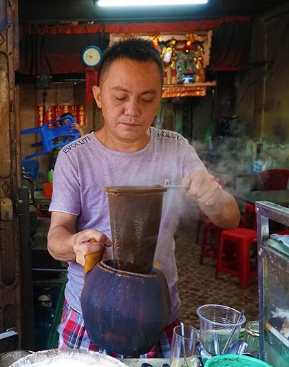 Anh Hùng tự tay chế từng mẻ cà phê bằng chiếc vợt quen thuộc. Ảnh: Phong Vinh.
