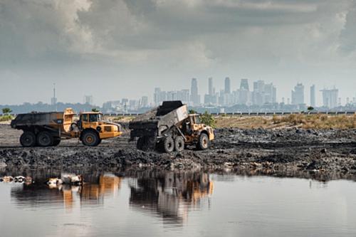 Xe đổ tro đốt rác xuống những hố chứa đặc biệt trên đảo. Ảnh:Eco-Business.