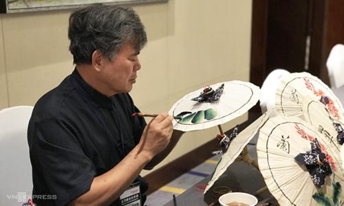 Nghệ nhân Đài Loan biểu diễn vẽ ô giấy trong buổi giới thiệu dự án mới tại Hà Nội.