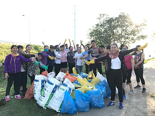 Nhóm cùng người dân thành phố Vinh nhặt rác thải bên bờ sông Lam. Ảnh: Nguyễn Thanh Tuấn Anh.