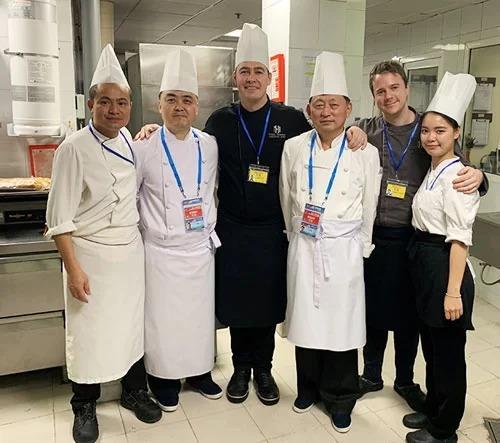 Bếp trưởng Paul Smart (thứ ba từ trái sang) chụp ảnh lưu niệm cùng đầu bếp Triều Tiên, phiên dịch và người giám sát của hai phía.