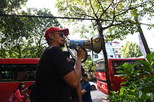 Cổ động viên dùng loa cầm tay gọi nhau lên xe bus.