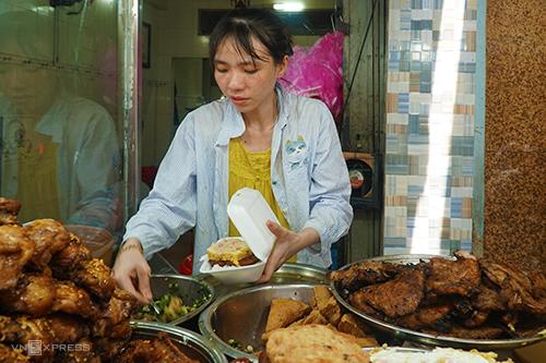 Chị Ngọc Châu, con gái chủ quán đang bán cơm cho khách mua mang về. Ảnh: Di Vỹ.