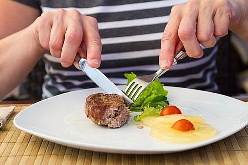 Để 2 tay trên bàn và giữa dao, dĩa bằng ngón trỏ là phép lịch sự cơ bản. Ảnh: Yury Minaev.