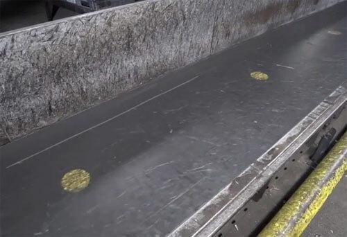 Các chấm vàng trên băng chuyền là vị trí đặt vali, để tránh tình trạng hành lý đặt lên đây bị tắc nghẽn do được xếp quá sát nhau. Ảnh: Sun.