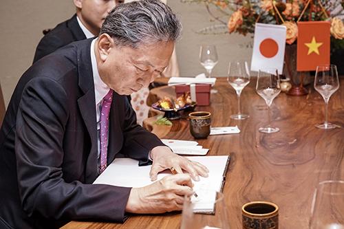 Cựu Thủ tướng Nhật Bản Yukio Hatoyama (giữa)ký lưu bút tặngnhà hàng ở Hà Nội.