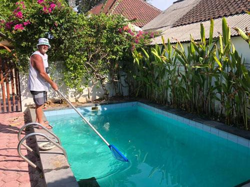 Garry đang làm sạch hồ bơi tại nơi mình nghỉ qua đêm. Ảnh: Facebook.
